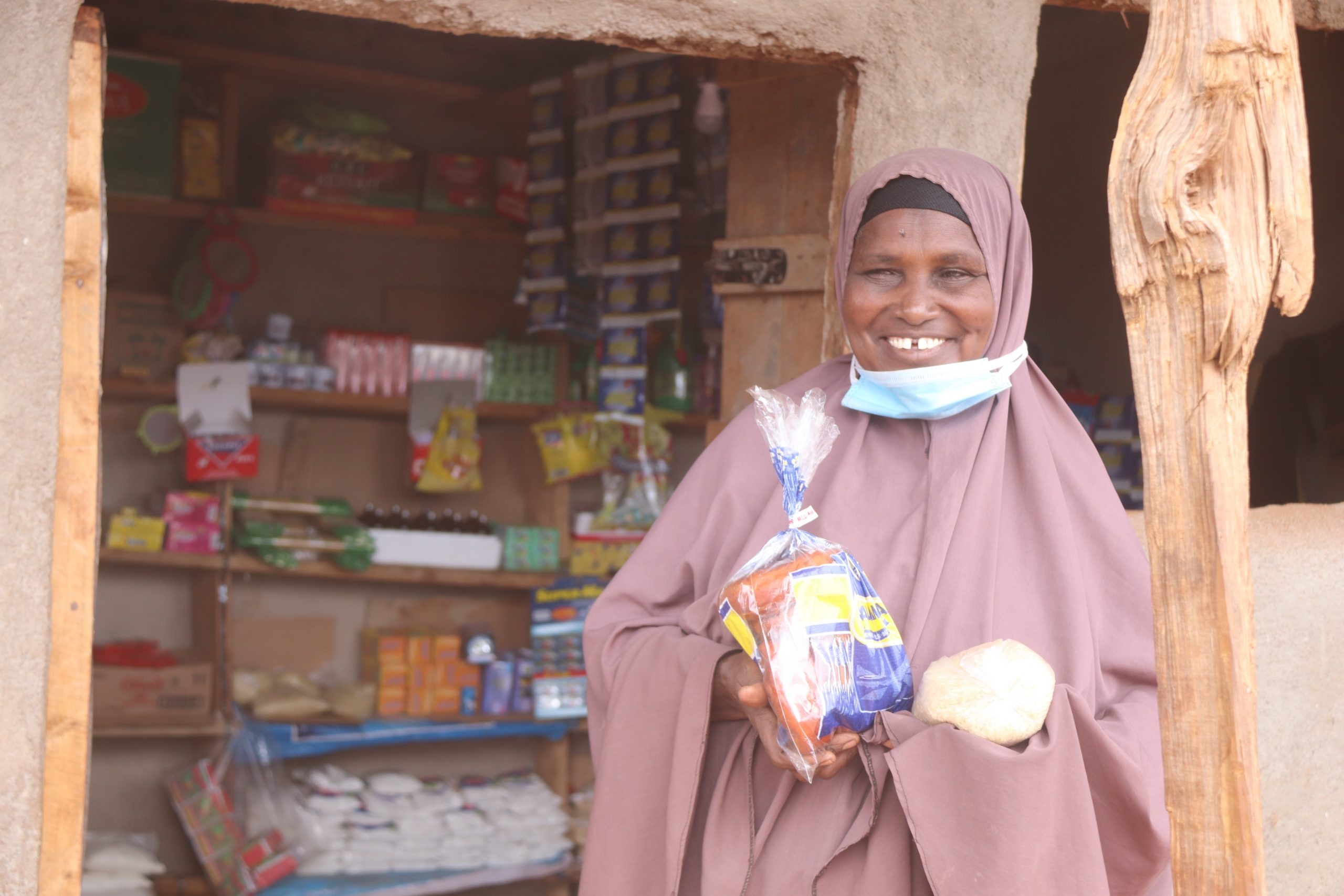 Photo/PACIDA: Halima Adan standing in front of her provision shop. She was given a business starter kit of Ksh.15, 000 from PACIDA through Kinisa Village Savings and Loans Association (VSLA) which she used to start her business.